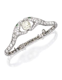 PLATINUM, DIAMOND AND EMERALD BRACELET. The opposing snakes centering an old mine-cut diamond weighing approximately 5.50 carats, accented by smaller old European and old mine-cut diamonds weighing approximately 6.45 carats, with two round emerald eyes, internal circumference 7 inches; circa 1925.