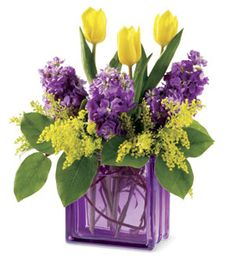 A sleek and modern glass block vase, in a rich shade of lavender and tulips, is filled with a lovely flower arrangement in harmonious shades of purple and yellow.