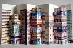 """upside town"" by paris-based designer mathilde nivet takes the context of urbanism and the city as the source for her work.   she uses a pop-up technique which combines folding, decoupage and montage to represent three-dimensional architecture at a large scale."
