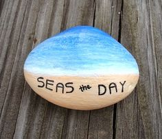 Seas the Day on a painted beach rock.