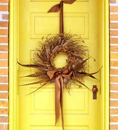 Fall wreath...love the feathers and the brown satin ribbon. Can I mention how much I LOVE that yellow door?