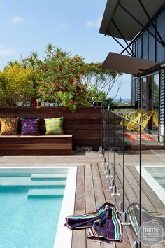 A colourful life: the shimmering pool is surrounded by three sides of timber fencing and a single wall of glass panels that allow for water views from inside the house.