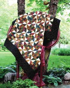 This stunning quilt is an easy one to make. Great for scraps, too. Half-square triangles and patchwork squares combine in a compelling quilt. Rich colors give it an elegant yet cozy look. Scrap Patch Paddlewheel Quilt