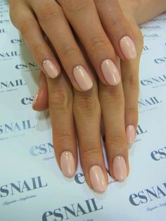 Pearly peachy almond shaped nails with simple crystal detailing by esNAIL