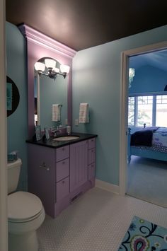 Painted cabinetry with dark countertop, decorative hardware, and crown molding above the mirror. Vanity lighting fixture mounted directly on arch mirror. Hexagon tile flooring. Painted decorative trim.