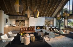 Designed for Megan Ralph Spaces for a safari guest lodge, these beautiful textured white ceramic wall tiles create visual intrigue above the fireplace in the guest area whilst beautifully complimenting the rest of the interior design.  #ceramic #wallpaper #design #interiordesign #architecture #southafrican #guesthouse #safari #decor #fireplace #tiles #wall #walltiles #featurewall #designideas #designinspo #homerenovations #hotel #renovations #bar