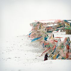 A man in the snow, via Flickr. Hundreds of prayer flags—a symbol of blessing in Tibet—offer colorful contrast to a stark winter scene. Image: Elaine Won