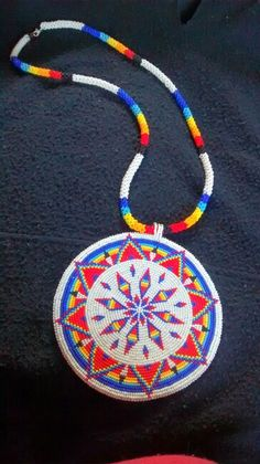 "Fully beaded medallion 5in round, size 12 cut beads with 31"" beaded rope chain with buckskin backing"