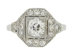 Art Deco diamond cluster ring. Set with a central cushion shape old cut diamond in an open back grain set millegrain box collet with a weight of 0.70 carats, encircled by a cluster of fourteen round old single cut diamonds in open back grain settings with fine rubover millegrain edging and a combined weight of 0.40 carats. The total approximate diamond weight is 1.10 carats, to an elegant octagonal cluster form with intricate openwork and tapered supportive shoulders, with a geometric…