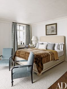 In another bedroom, the bespoke bed is upholstered in a Rogers & Goffigon linen and dressed with a faux-fur coverlet by Lazarine; the armchairs are clad in a Jasper fabric, and the carpet is by the Rug Company.