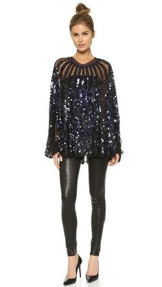 Get New Year's Eve sparkle without freezing! Try a sequined top (like this one from the Christophe Sauvat Collection) with leather leggings and smart black pumps. A top knot and delicate stud earrings complete the look!