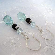 Fancy Aqua Glass Quartz faceted teardrops wire-wrapped with sterling silver, accompanied by Smoky Quartz heishi, Bali silver, and Light Azore Swarovski crystals. Hand-formed sterling silver ear wires complete them. Lovely, one of my favorite combinations. Measures just under 2 inches in length from top of ear wire to bottom of bead. Promptly made to order and quickly shipped.
