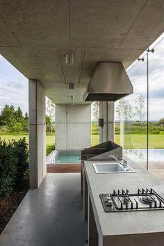 Architekt originálně propojil exteriér domu s interiérem. Betonová stropní deska vybíhající až nad bazén chrání část vodní plochy, ale především venkovní kuchyni, navazující na tu uvnitř domu. Pobyt venku a společné vaření si tak rodina může užívat, jak nejdéle to jde.