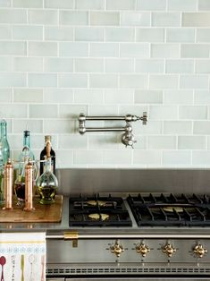 Glass subway tile backsplash in this French Country home designed by Alice Lane Interior Design. || Range Lacanche