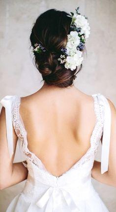 { Bride's low looped bun with side flower crown }