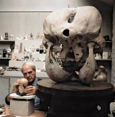 Henry Moore working on the maquette for Atom Piecem alongside an elephants head at his studio in Much Hadlam 1970
