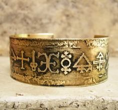 Etched Brass Cuff with Alchemy Symbols- what do the symbols means? Why was it made? Who wears it?