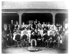 "Hudson Company Band, gathered together on the steps of the Belle Isle Casino. Musicians are seated with their instruments in the first row, and others, including a police officer, waiters, and bartenders are gathered behind. Hand-written on the verso, ""J.L. Hudson Band - Belle Isle Casino - 1893."""