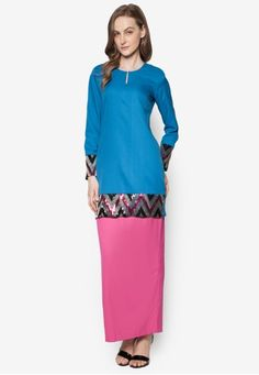Baju Kurung Modern from Gene Martino in Pink and Blue Deck yourself with solid shades this Raya with Gene Martino. The brand reinvents the evergreen Baju Kurung Modern with elaborate sequins by the sleeve ends and hemline for added style. Complete with soft gold threads and a contrasting skirt, topp... #bajukurung #bajukurungmoden