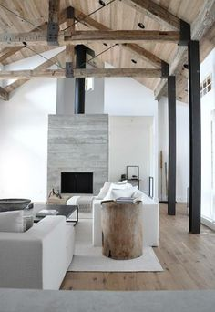 love the ceiling bracing, simple use of material and colour, vertical stone-faced fireplace