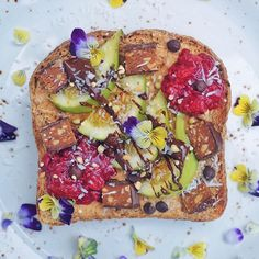 """Happy Toast Tuesday, gorgeous people! This toast 🍞🍞 combo is sweet enough for dessert but healthy enough for breakfast.  Gluten-free toast topped with almond butter, homemade red currant jam, green figs, dark 🍫🍫 drizzle, seeds, vegan chocolate chips, edible flowers, shredded coconut, and chocolate-coated almond spice protein squares from @squareorganics. Best tasting protein bar ever 👌🏽👌🏽 And you can get 20% off your order on www.squareorganics.com using the code """"paleoandplants.""""…"""