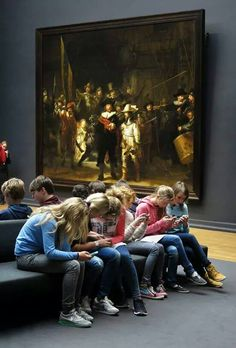 """Group of teenagers checking their cell phones while sitting next to Rembrandt's """"Night Watch"""""""