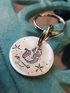 Aluminum keychain with a mermaid, i have handstamped Mermaid Soul on it. it has a cute mermaid on it, let me know what you would like on yours. Aluminum it is a light metal but it is thick. Tag is approximately 1 inch wide. I have another mermaid keychain....