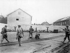 Soldiers from the 157th US Infantry Regiment execute the SS guards from the German Dachau – death camp. In the center of the photo the 7.62 mm Browning M1919A4 light machine gun.