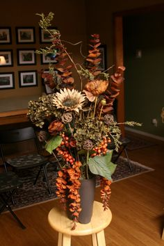 Floral arrangement for fall with orange, dark green, and off-white    Designed by: Create+Design