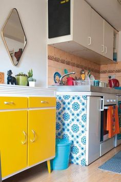 From Hannah Zakari. Love the yellow and white cabinets