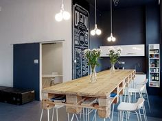 Industrial elements such as a sliding door, exposed lighting and rustic table pair well with the modern white bar stools and built-ins.