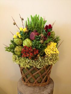 Custom dried floral arrangement in glass woven basket with berry sticks, clover, pomegranate, artichokes, clovers, tortum, china millet, hydrangea, semprevivo and preserved boxwood.