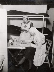 Two nurses carrying out administration work at the Medical Aid Centre at Notting Hill Gate air raid shelter during the Second World War. Some bunk beds are immediately behind them.    Photographed by Topical Press, 13 Dec 1940