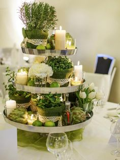 A three-tiered dessert tray is a great tool for displaying a pretty grouping of candles and greenery. Add visual interest by using herbs and vegetables with different textures, like the artichokes displayed here.