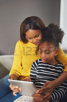 Afro american woman and child with tablet sitting in a sofa Stock Photo