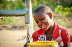 Suzana Ricardo is all smiles as she fetches clean and safe water from the borehole drilled by World Vision in Saua-Saua ADP in Mozambique. Photo: 2014 Antonio Matimbe/World Vision #WaterEffect