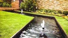 """Estanque, canal y fuentes de diseño contemporáneo. Un """"gran canal"""" que recorre longitudinalmente el jardín, bajo las tarimas que permiten disfrutar de él y que nos sugieren un río que fluye y se pierde bajo nuestros pies."""