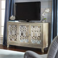Modern lines mix with a vintage-inspired design to create our striking TV stand. Mirrored doors add to the dramatic and elegant style while the soft, whitewash finish is the final touch.  It's so pretty you might even forget to watch TV and admire your lovely cabinet instead.