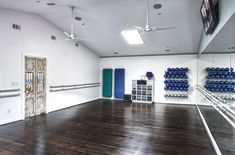 White walls and ceilings and dark floors with mirrors ballet bars and storage