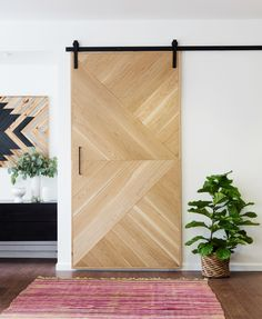 """""""Mix natural wood with clean, white walls,"""" Nelson says. """"Here, the unfinished white oak paired with the matte black hardware creates a nice contrast, adding interest to the space."""""""