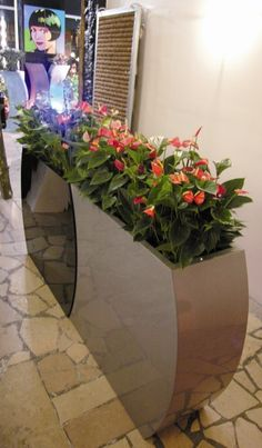 Curvy barrier planter in metallic silver, planted with red anthuriums
