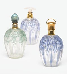 "René Lalique THREE ""D'ORSAY"" PERFUME BOTTLES each with stopper each molded LALIQUE MADE IN FRANCE and engraved made in France frosted and molded glass with blue and green patiné and gilt metal"