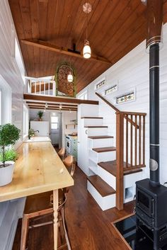 """The kitchen features a double ceramic apron sink, custom wood countertops, and full size appliances including a refrigerator, 30"""" propane oven with hood vent, and dishwasher."""