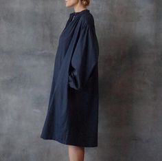 """Black Crane Tulip dress is a blousy knee length A-line dress. Pair this dress with camel colored booties for the perfect fall outfit. The Tulip dress has billowy sleeves with fine gathering at the cuffs. Gathered pleating around shoulders and dolman style collar. Side pockets with straight hem. Color is Midnight Blue. 100% Cotton 100% produced in Los Angeles Model is 5'8"""" and wearing size Small"""