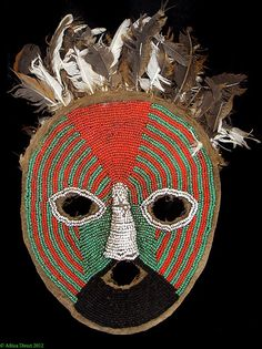Africa | Beaded mask from the Tabwa people of DR Congo | Made of class beads stitched onto raffia and cotton cloth, surmounted with feathers | 2nd half of the 20th century: