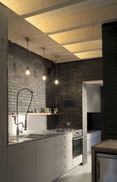 nowoczesna szara kuchnia z ciemnoszarą cegłą na ścianie, drewnianym sufitem i żarówkami na kablach