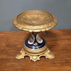 Fraaie antieke metalen vergulde tazza met handbeschilderd porseleinen tussenstuk. De conditie is perfect. Afmetingen: 16 x 16 cm.