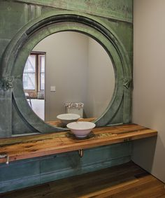 Large Round Mirror - with great architectural details: The powder room mirror was a salvaged copper window surround sourced by Urban Archaeology who also fabricated additional pieces of copper to clad the entire wall. #Mirror #PowderRoom #Inspiration