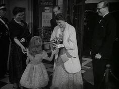 The Queen accepts a bouquet of flowers from Brigitte Fossey at the premiere of the film, Les Belles de Nuit. 1953.