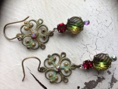 Glass olivine and ruby stones with filigree verdigris dangles and aurora borealis crystals $28